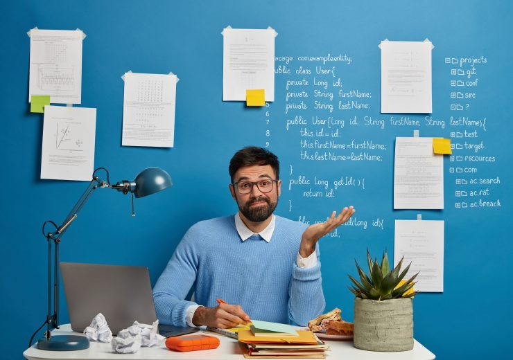 Skilled young IT professional works on programming new useful web application, raises palm with hesitation, writes down necessary information on paper, work with modern gadget in coworking space